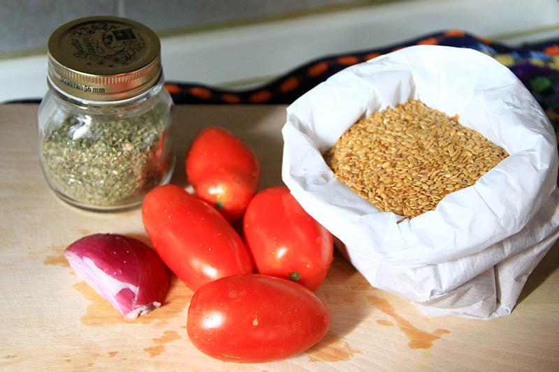 Semi lino, pomodori, origano e cipolla sopra un tagliere