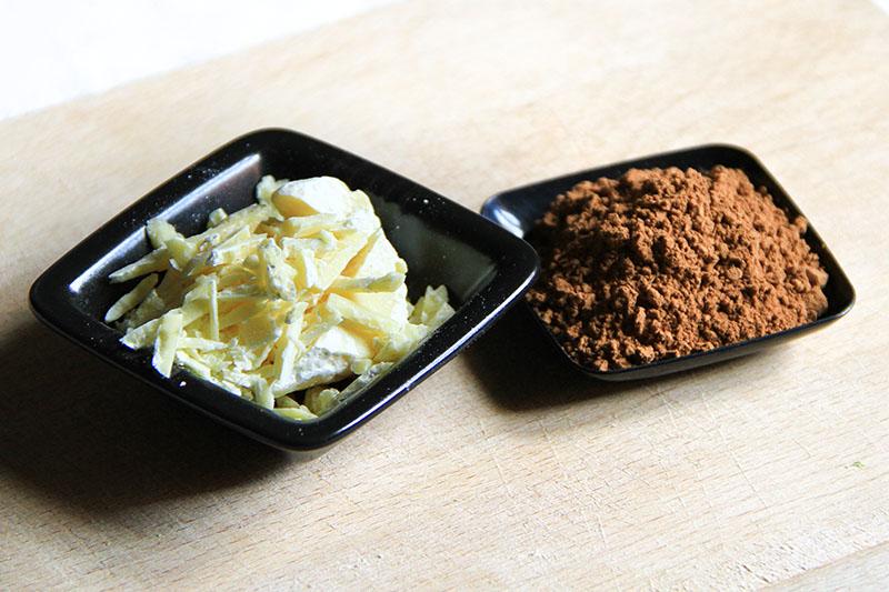Burro di cacao e farina di carruba all'interno di ciotoline nere sopra un tagliere di legno.