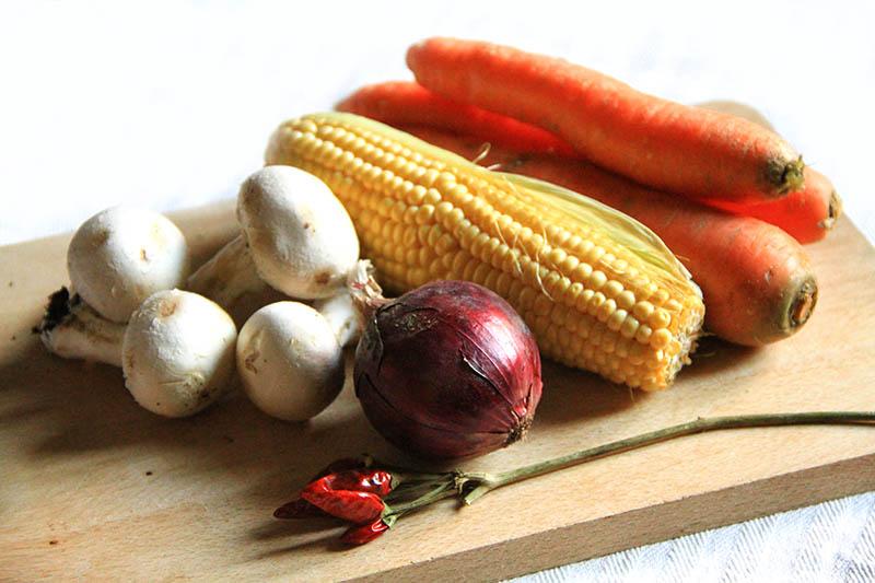 Funghi, cipolla, mais, carote e peperoncino su un tagliere