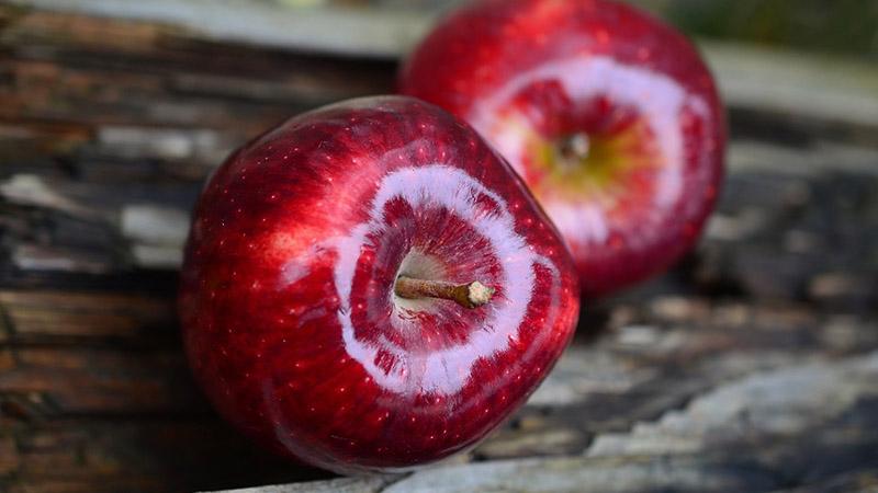 Due mele su un ripiano di legno scuro