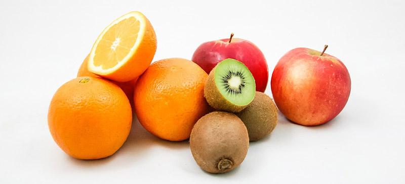 Arance mele e kiwi su sfondo bianco
