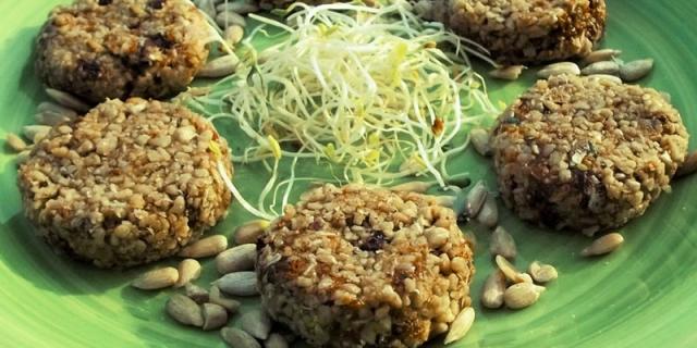 Biscotti crudisti ai semi di girasole su un piatto verde, con germogli al centro