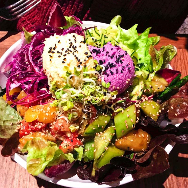 Un'insalata colorata con 2 diversi hummus