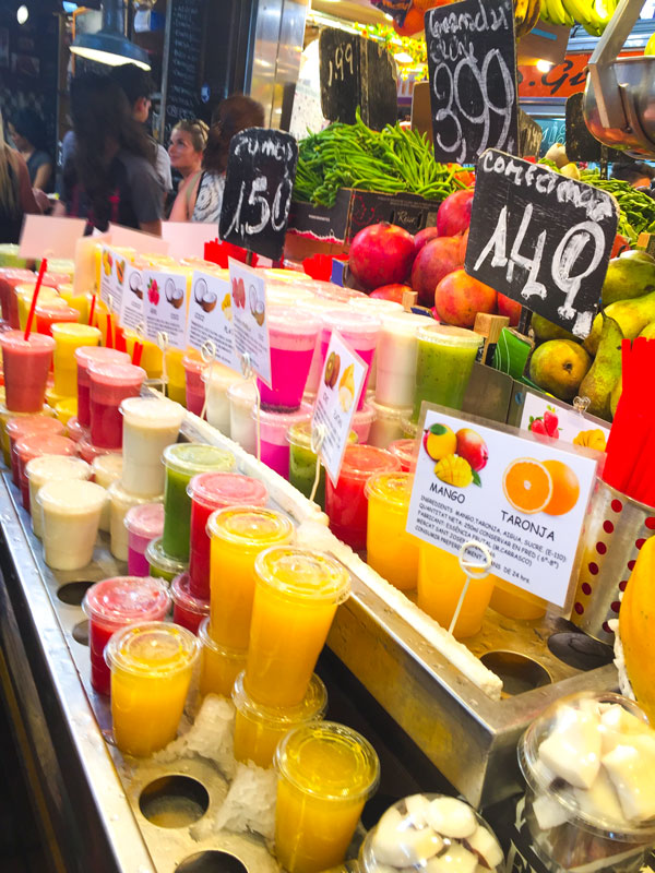 Succhi di frutta colorati disposti su ripiani al mercato