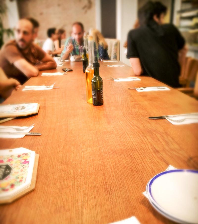 Un lungo tavolo di legno chiaro e alcune persone