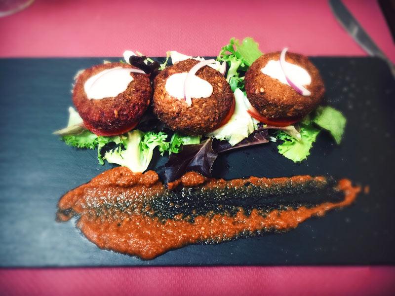 Un piatto nero con 3 burger adagiati su un letto d'insalata e una salsa rossa