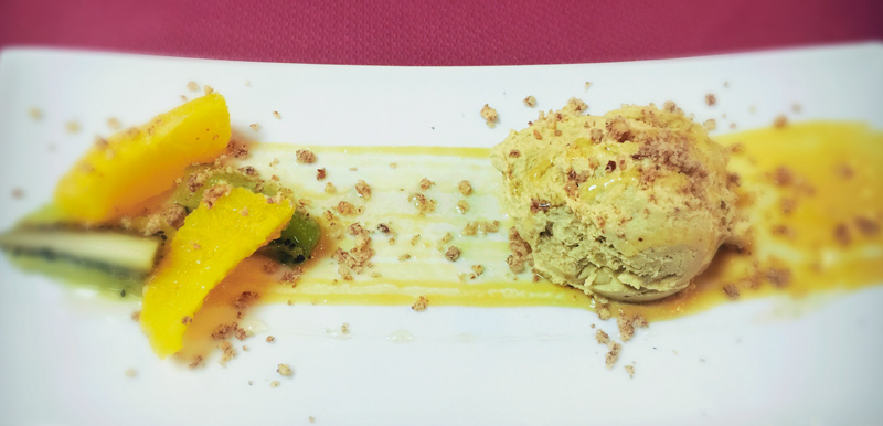 Un piatto bianco con a sinistra alcuni pezzi di frutta e a destra un gelato verde con granola