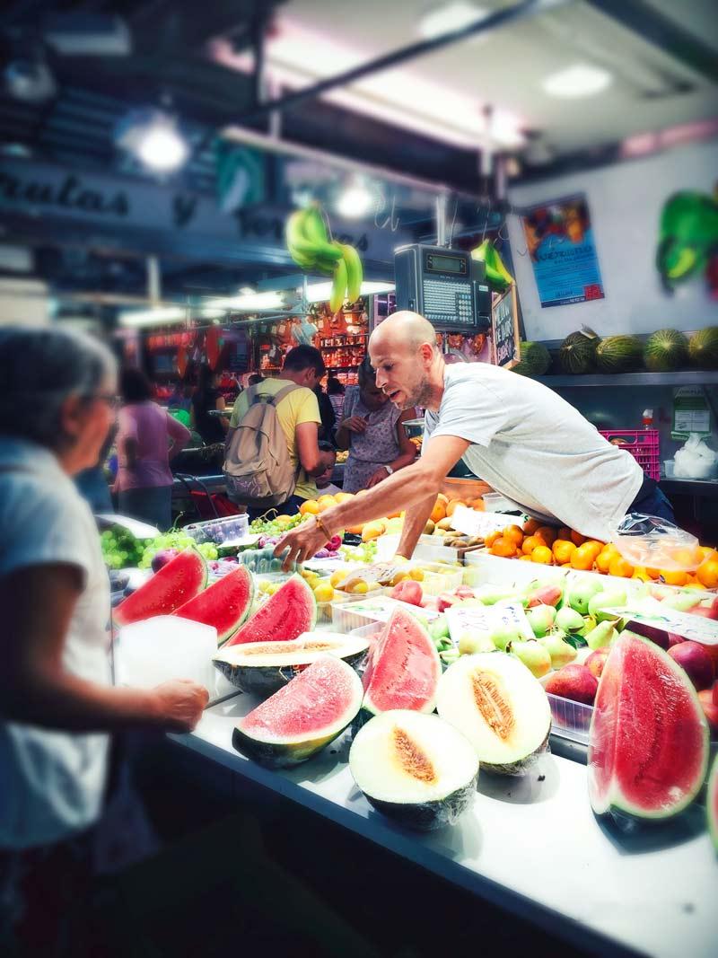 Il proprietario di un banco frutta mostra alcune fette di cocomero ad un acquirente