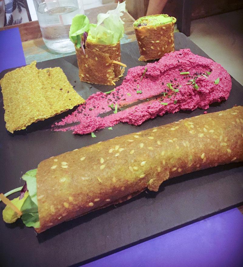 Roll di semi e humus rosa su un piatto nero