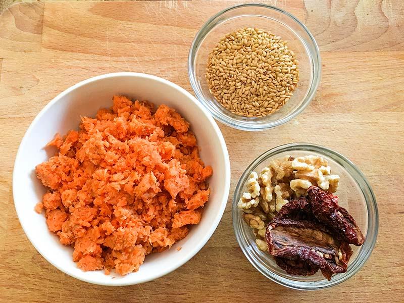 3 ciotole contenenti la polpa di carote, i semi di lino, le noci e i pomodori secchi