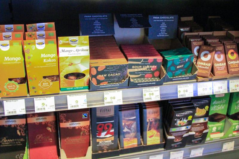 scaffale di negozio con confezioni di cioccolate di diverso colore e formato