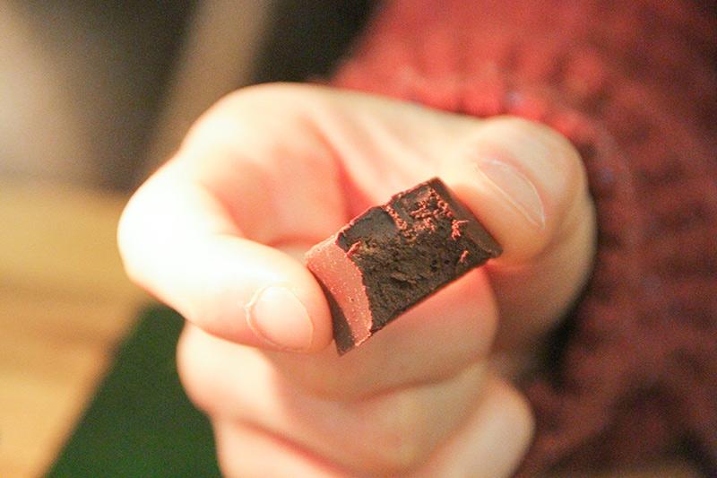 Un cioccolatino morsicato tenuto tra 2 dita