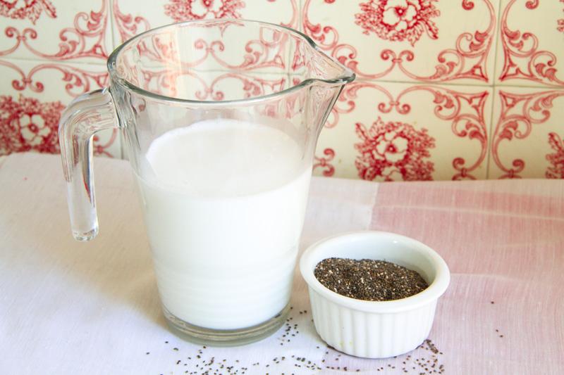 Una brocca di vetro piena di latte e una ciotola di ceramica bianca piena di semi di chia