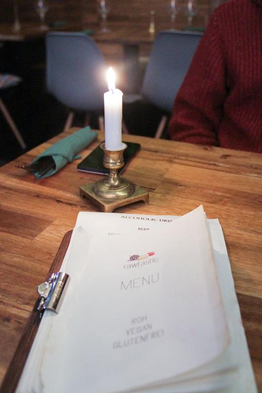 Menù su tavolo di legno, illuminato da candela