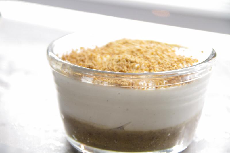 Panna cruda di colore bianco in piccola coppetta di vetro e topping di granella