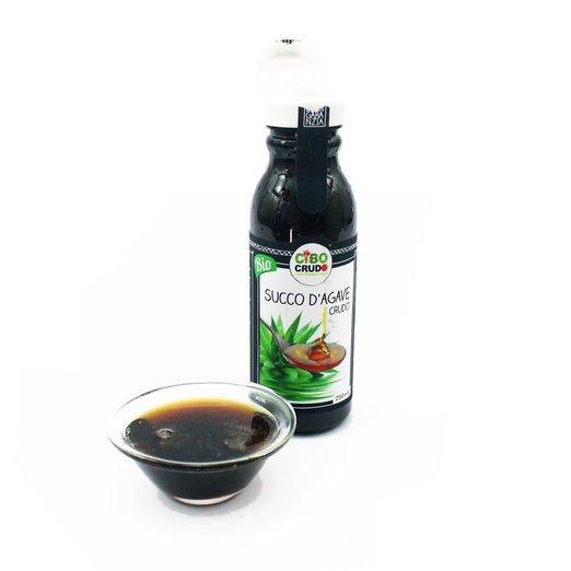 una bottiglietta scura con etichetta succo d'agave e una ciotolina di vetro con del succo scuro dentro