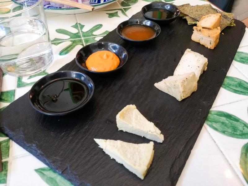 Piatto piano nero per i formaggi crudisti con ciotole per le salse