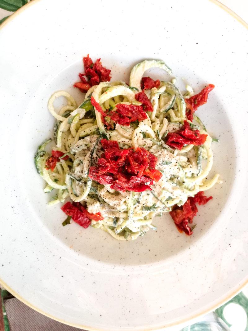 Piatto bianco con spaghetti di zucchina e battutto di pomodorini secchi