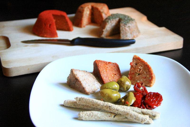 Un piatto con 3 fette di formaggi crudisti, grissini, alcune olive e pomodori secchi