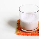 Un bicchiere di latte di mandorle con 7 mandorle al suo fianco