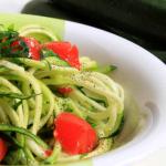 Semplici spaghetti di zucchine crudi in un piatto, decorati con prezzemolo e pomodori
