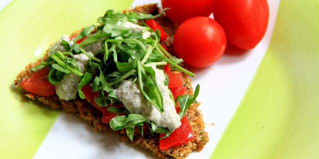 pizza di semi di lino di colore beige condita con pomodorini, rucola e formaggio bianco crudo, sullo sfondo tre pomodorini.