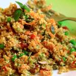 Cous cous di cavolfiore, condito con verdure colorate, su di un piatto verde con accanto una forchetta