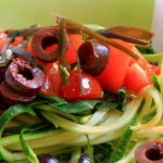 Spaghetti di zucchine crudi, realizzate con apposito strumento, conditi con pomodori, olive e alghe,
