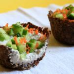 due capcakes su sfondo bianco, ripieni di maionese cruda di semi di girasole e decorati con pezzettini di cetriolo e carota grattuggiata