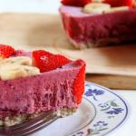 Una fetta di semifreddo0 di frutta dal colore rosa intenso in primo piano, sullo sfondo l'intera torta