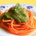 Spaghetti di carote, conditi con pesto di menta e zucchine dal colore verde intenso, posti su un piatto bianco dai decori blu