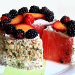 Torta di anguria ricoperta di panna crudista alle mandorle, decorata con frutta fresca e noci.