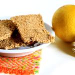 Biscotti di sesamo e zenzero dalla forma rettangolare, adagiati su un piattino bianco, accanto un limone e un pezzo di radice di zenzero