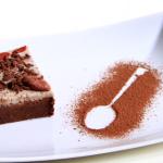 Una fetta di torta al cioccolato, decorata con bacche di goji, bacche di cacao e scaglie di cioccolato, su un piatto bianco.