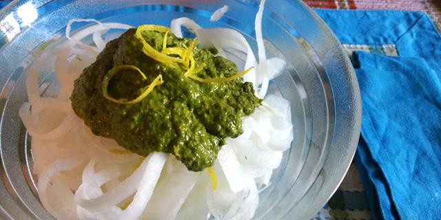 In una ciotola di vetro sono presenti spaghetti di daikon conditi con pesto di rucola e scorze di limone