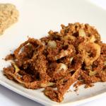 Su di un piatto bianco un mucchietto di cipolle croccanti e dorate, sullo sfondo una salsa da accompagnamento