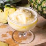 Una coppa di vetro contenente una granita di anans. Sullo sfondo anans tagliato.