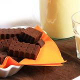 Una bottiglia di latte vegetale, un bicchiere quasi pieno e una ciotolina rettangolare che accoglie i biscotti dal colore marrone scuro