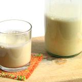 Un bicchiere di latte mezzo pieno accanto ad una bottiglia di latte vegetale.