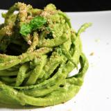 Spaghetti di zucchina arrotolati su un piatto bianco; decorati con qualche fogliolina di basilico e gocce di olio.