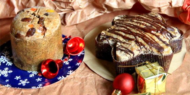 Panettone e pandoro crudisti presentati con varie decorazioni natalizie sullo sfondo.