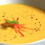Vellutata di carote all'interno di un piatto bianco, decorata con striscioline di carota e prezzemolo fresco