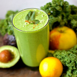 Un bicchiere di vetro con uno smoothie verde. Intorno avocado, limone, mela e cavolo riccio.