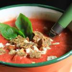 Una ciotola con della Zuppa di pomodoro, decorata con foglie di basilico e crostini di pane crudista.