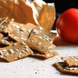 Cracker crudisti alla pizzaiola su un tagliare di legno, accanto due pomodori rossi.